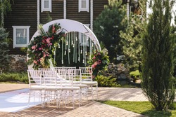 Wedding arch in the form of a white moon with floral compositions in a tropical style with leaves of a monster decorated with light bulbs. Transparent chairs for a ceremony in the street in the summer