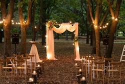 Wedding arch in the woods with light bulbs. Beautiful wedding rustic in the forest. Seats for guests at a beautiful wedding with light bulbs in the forest.