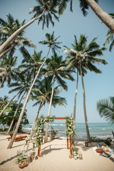 Wedding arch on a white sand beach. Palm trees sea and white sand beach