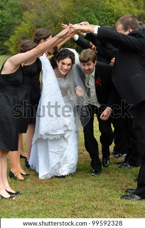 Wedding attendants form gauntlet line and bride and groom dance beneath their joined hands.  Wedding is over and celebration has begun.