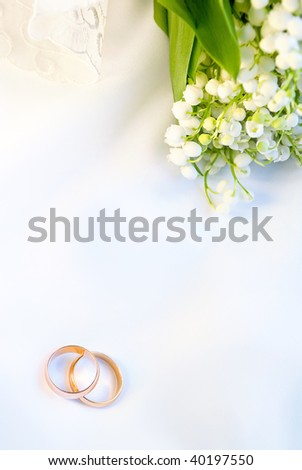 Wedding background with rings and lilies of the valley