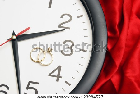 Wedding bands rest on the face of a clock to represent that its time to tie the knot. - stock photo
