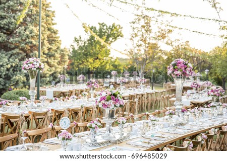 Wedding. Banquet. Chairs and honeymooners table decorated with candles, served with cutlery and crockery and covered with a tablecloth. The table stands on a green lawn in the backyard banquet area. #696485029