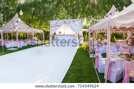 Wedding banquet outdoor in marquees on lawn decorated pink silk, lace and flowers #714349624
