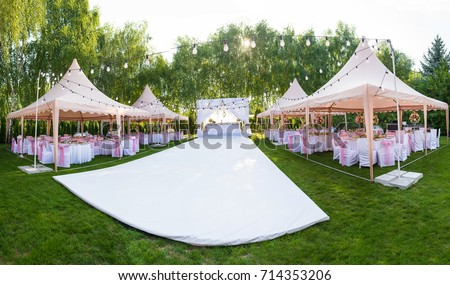Wedding banquet outdoor in marquees on lawn decorated pink silk, lace and flowers #714353206