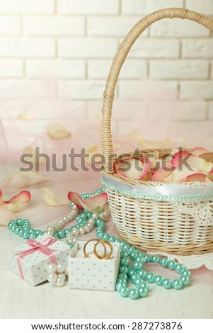 Wedding basket with roses petals on table, on light background