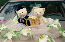 Wedding bears are sitting on the hood of a wedding car. Wedding toys. Winnie the Pooh and Piglet. Love.