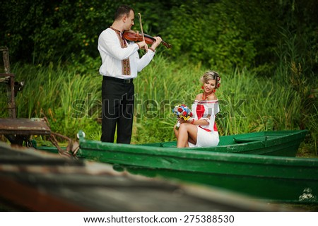 Wedding beautiful couple in traditional dress on the dock . Groom playing the violin