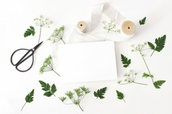 Wedding, birthday desktop stationery mock-up scene. Blank greeting card, black vintage scissors, silk ribbon and cow parsley leaves, flowers. White table background. Horizontal flat lay, top view.