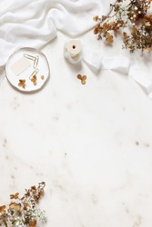 Wedding, birthday stationery styled stock photo. White table runner, porcelain plate with stamp, golden clips, silk ribbon, dry hydrangea, gypsophila flowers. Marble stone background. Vertical flatlay