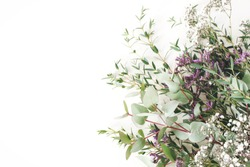 Wedding, birthday styled stock photo. Feminine scene, floral composition. Bunch of eucalyptus branches, baby's breath Gypsophila and limonium flowers. White table background. Flat lay, top view.