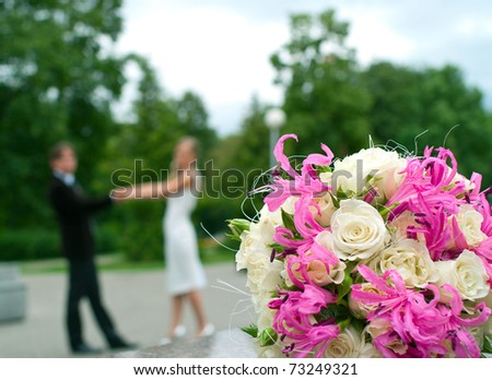 Wedding bouquet against young couple. Shallow DOF