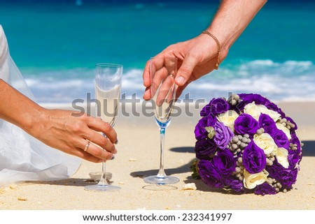 Wedding bouquet and two glasses of champagne on the sand. Male and female hands with wedding rings are drawn to the glass. Blue sea in the background.