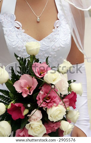 wedding bouquet from colorful roses in hand of the bride.