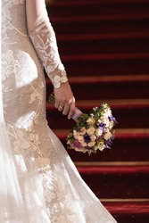 Wedding bouquet in a hand of a bride with red stairs in the background