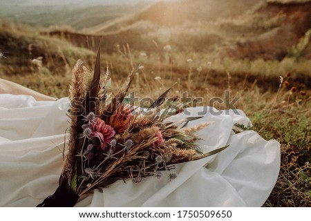 wedding bouquet in boho style collected from wild flowers, the bride holds a bouquet in her hand, in nature, white dress, live plants, a composition of dried flowers
