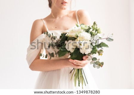 wedding bouquet in cream shades with eucalyptus, the bride is smiling and holding a bouquet, cream wedding bouquet #1349878280