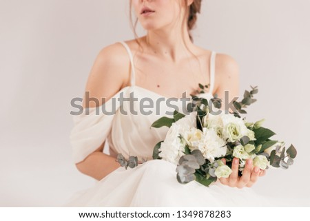 wedding bouquet in cream shades with eucalyptus, the bride is smiling and holding a bouquet, cream wedding bouquet #1349878283