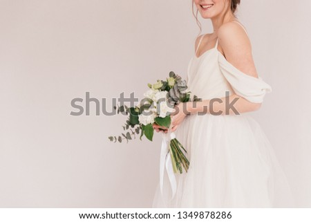 wedding bouquet in cream shades with eucalyptus, the bride is smiling and holding a bouquet, cream wedding bouquet #1349878286