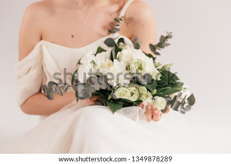 wedding bouquet in cream shades with eucalyptus, the bride is smiling and holding a bouquet, cream wedding bouquet #1349878289