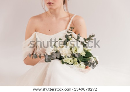 wedding bouquet in cream shades with eucalyptus, the bride is smiling and holding a bouquet, cream wedding bouquet #1349878292