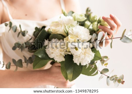 wedding bouquet in cream shades with eucalyptus, the bride is smiling and holding a bouquet, cream wedding bouquet #1349878295