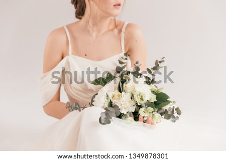 wedding bouquet in cream shades with eucalyptus, the bride is smiling and holding a bouquet, cream wedding bouquet #1349878301