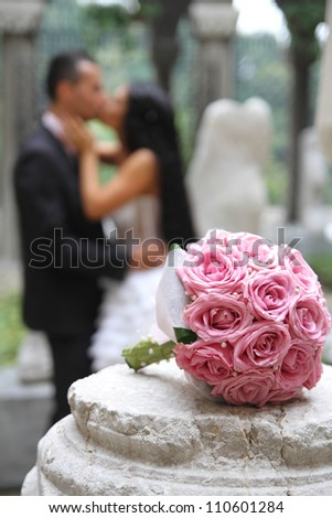 Wedding bouquet  in focus and couple in the background