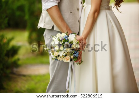 Wedding bouquet in hands of bride and groom in wedding day #522806515