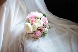 Wedding bouquet lies on the veil