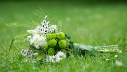 wedding bouquet lying on green grass, white and green flower in bouquet, banner copy space