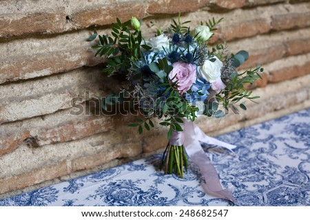 Wedding bouquet of bride. Bridal flowers bouquet in wedding day with blue, white, pink, and green flowers over brick wall