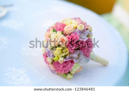 Wedding bouquet of bride - colorful flowers pink, white roses and yellow freesia lying on table at wedding on nature at summer day. Classic and elegant bridal decoration. close up of wedding bouquet