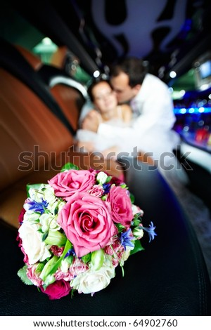 Wedding bouquet of flowers in limo and happy bride and groom