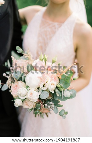 Wedding bouquet of peony rose, rose and eucalyptus in the hands of the bride. European style wedding. Selected focus and blurred background. Сток-фото ©