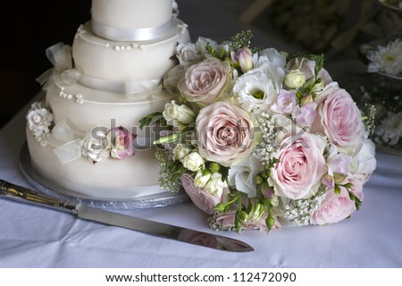 wedding bouquet of pink and white roses alongside the cake - stock photo