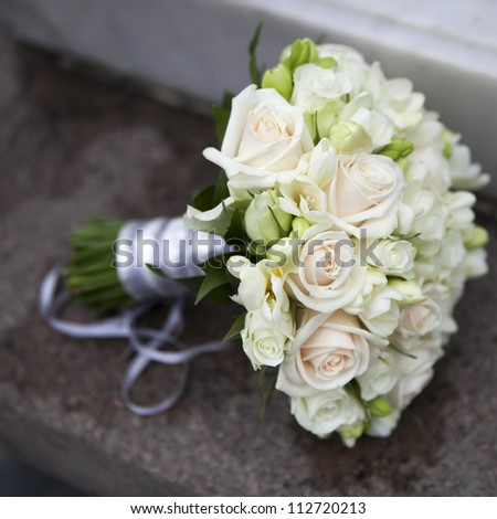 Wedding bouquet of pink and white  roses and blue fresia  lying on bench