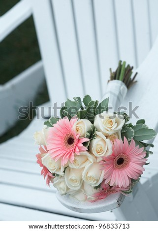 Wedding bouquet of pink daises and white roses on beach chair