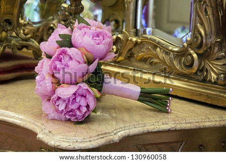 Wedding bouquet of pink peony flowers on antique dressing table with mirror.