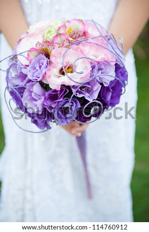 Wedding bouquet of purple and pink flowers in the hands of the bride
