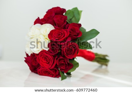 Wedding bouquet of red and white roses on a light background #609772460