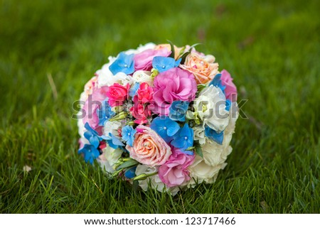 wedding bouquet of the bride- colorful wedding flowers at the grass. Elegant and classic bridal decoration with amazing blue,pink,violet and cream colored roses,fresia and ranunculus for marriage