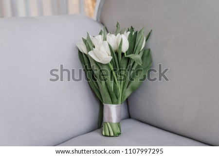 Wedding bouquet of tulips lying on the chair close-up. The bride's bouquet.  #1107997295