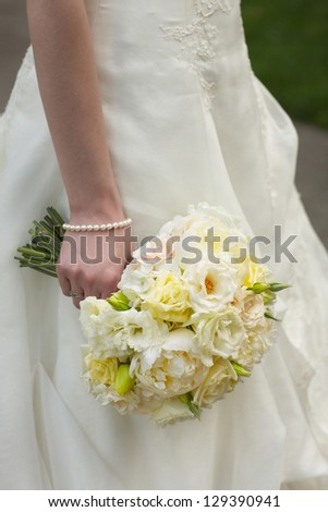 Wedding bouquet of white and yellow roses held by bride