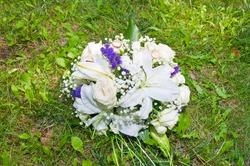 Wedding bouquet of white roses and purple irises.