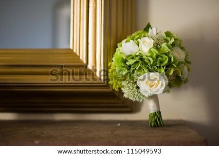 wedding bouquet of white roses with gold frame mirror and shelf
