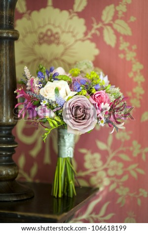 wedding bouquet on a wooden shelf with vintage patterned wallpaper