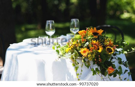 Wedding bouquet over white table outdoor.