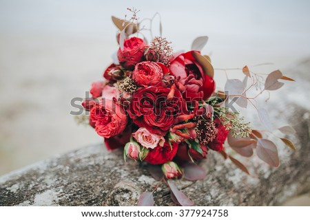 Wedding bouquet . The bride\'s bouquet. Bouquet of red and pink flowers, black berries and greenery, with a ribbon of color Marsala lies on a log by the lake