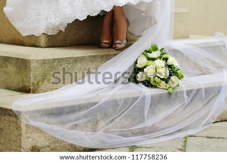 Wedding bouquet with Bride veil on the stairs in landscape orientated photo, focused to the Wedding bouquet